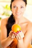 Mujer joven hermosa que sostiene una naranja Fotografía de archivo