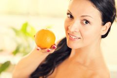 Mujer joven hermosa que sostiene una naranja Imágenes de archivo libres de regalías