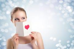 Mujer joven hermosa que sostiene una postal de la tarjeta del día de San Valentín Fotografía de archivo