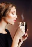 Mujer joven hermosa que sostiene una taza de café con los ojos cerrados Fotografía de archivo