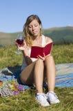 Mujer joven hermosa que tiene comida campestre en el prado, libro de lectura, SMI imagen de archivo libre de regalías