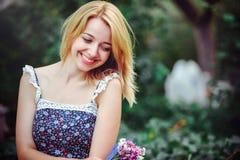 Mujer joven hermosa que tiene una comida campestre en el campo Día acogedor feliz al aire libre abierto La mirada sonriente sonri Fotografía de archivo libre de regalías