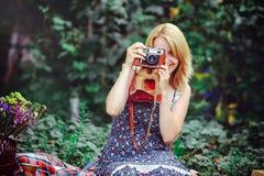 Mujer joven hermosa que tiene una comida campestre en el campo Día acogedor feliz al aire libre abierto La mujer sonriente con la Imagen de archivo