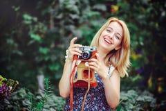 Mujer joven hermosa que tiene una comida campestre en el campo Día acogedor feliz al aire libre abierto La mujer sonriente con la Fotografía de archivo