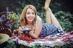 Mujer joven hermosa que tiene una comida campestre en el campo Día acogedor feliz al aire libre abierto La mujer sonriente con la Fotos de archivo libres de regalías