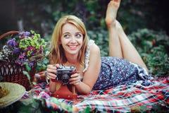 Mujer joven hermosa que tiene una comida campestre en el campo Día acogedor feliz al aire libre abierto La mujer sonriente con la Foto de archivo