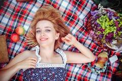 Mujer joven hermosa que tiene una comida campestre en el campo Día acogedor feliz al aire libre abierto La mujer sonriente miente Foto de archivo