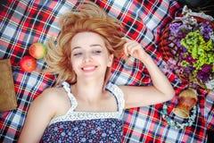 Mujer joven hermosa que tiene una comida campestre en el campo Día acogedor feliz al aire libre abierto La mujer sonriente miente Fotos de archivo libres de regalías