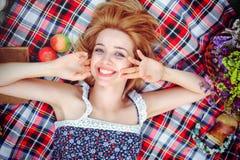 Mujer joven hermosa que tiene una comida campestre en el campo Día acogedor feliz al aire libre abierto La mujer sonriente miente Imagen de archivo