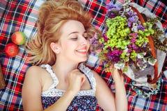 Mujer joven hermosa que tiene una comida campestre en el campo Día acogedor feliz al aire libre abierto Mentiras y sonrisas sonri Fotos de archivo