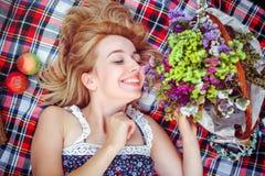 Mujer joven hermosa que tiene una comida campestre en el campo Día acogedor feliz al aire libre abierto Mentiras y sonrisas sonri Fotografía de archivo