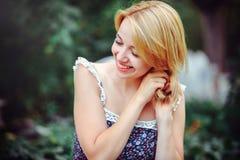 Mujer joven hermosa que tiene una comida campestre en el campo Día acogedor feliz al aire libre abierto Pelo conmovedor sonriente Foto de archivo