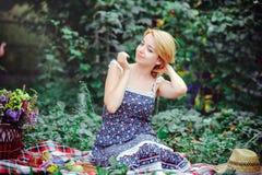 Mujer joven hermosa que tiene una comida campestre en el campo Día acogedor feliz al aire libre abierto Pelo conmovedor sonriente Imagenes de archivo