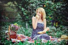 Mujer joven hermosa que tiene una comida campestre en el campo Día acogedor feliz al aire libre abierto Mujer sonriente que come  Imagen de archivo