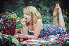 Mujer joven hermosa que tiene una comida campestre en el campo Día acogedor feliz al aire libre abierto Mujer sonriente que come  Fotos de archivo
