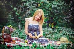 Mujer joven hermosa que tiene una comida campestre en el campo Día acogedor feliz al aire libre abierto Mujer sonriente con el li Imagen de archivo libre de regalías