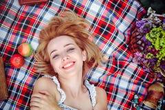 Mujer joven hermosa que tiene una comida campestre en el campo Día acogedor feliz al aire libre abierto Una mujer sonriente mient Fotografía de archivo