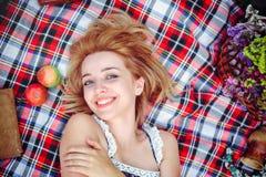 Mujer joven hermosa que tiene una comida campestre en el campo Día acogedor feliz al aire libre abierto Una mujer sonriente mient Imagen de archivo libre de regalías