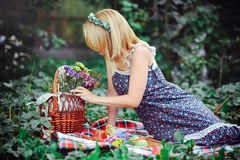 Mujer joven hermosa que tiene una comida campestre en el campo Día acogedor feliz al aire libre abierto Mujer sonriente que mira  Fotos de archivo libres de regalías