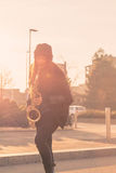 Mujer joven hermosa que toca el saxofón del tenor Foto de archivo libre de regalías