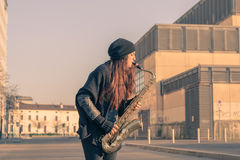 Mujer joven hermosa que toca el saxofón del tenor Imagen de archivo