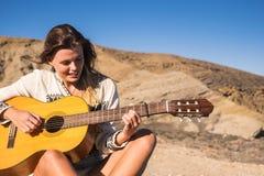 Mujer joven hermosa que toca la guitarra al aire libre Foto de archivo libre de regalías