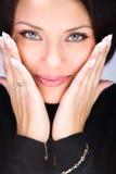 Mujer joven hermosa que toca su cara por las manos Foto de archivo