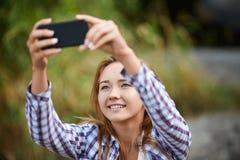 Mujer joven hermosa que toma el cuadro de se Selfie en un fondo natural borroso Imagen filtrada Imagenes de archivo