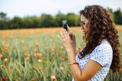 Mujer joven hermosa que toma imágenes de un campo de la amapola fotos de archivo
