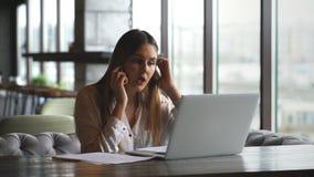 Mujer joven hermosa que trabaja con el ordenador portátil y que habla en el smartphone que habla con el cliente que se sienta cer almacen de metraje de vídeo
