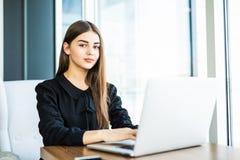 Mujer joven hermosa que trabaja en el ordenador portátil y que mira la cámara en café Imagen de archivo libre de regalías