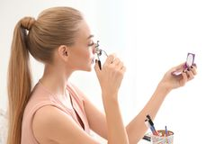 Mujer joven hermosa que usa el bigudí de la pestaña foto de archivo