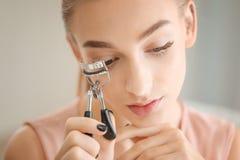 Mujer joven hermosa que usa el bigudí de la pestaña imágenes de archivo libres de regalías