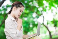 Mujer joven hermosa que usa el ordenador portátil en al aire libre Foto de archivo libre de regalías
