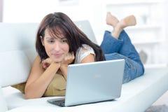 Mujer joven hermosa que usa el ordenador portátil en el sofá Fotos de archivo