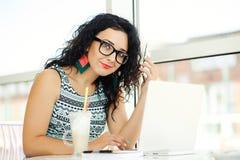 Mujer joven hermosa que usa el ordenador portátil y hablando en el teléfono móvil Fotografía de archivo