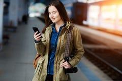 Mujer joven hermosa que usa el Smart-teléfono mientras que se coloca en la plataforma del ferrocarril Foto de archivo libre de regalías