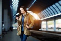 Mujer joven hermosa que usa el Smart-teléfono mientras que se coloca en la plataforma del ferrocarril Imagenes de archivo