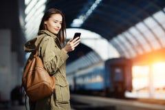 Mujer joven hermosa que usa el Smart-teléfono mientras que se coloca en la plataforma del ferrocarril Fotografía de archivo