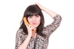 Mujer joven hermosa que usa el teléfono anaranjado retro Imagenes de archivo