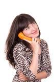 Mujer joven hermosa que usa el teléfono anaranjado retro Imagen de archivo libre de regalías