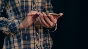 Mujer joven hermosa que usa el teléfono elegante con el fondo negro almacen de video