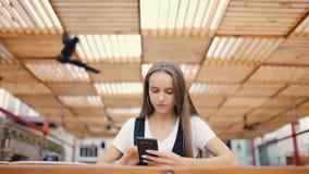 Mujer joven hermosa que usa el teléfono elegante moderno en el café y mecanografiando el mensaje de texto en el teléfono móvil metrajes