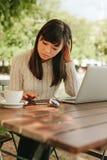 Mujer joven hermosa que usa el teléfono móvil en el café Imagen de archivo libre de regalías
