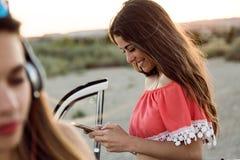 Mujer joven hermosa que usa el teléfono móvil en viaje por carretera Foto de archivo
