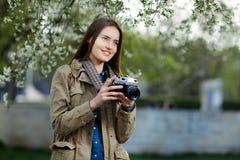 Mujer joven hermosa que usa la cámara de la foto del vintage en el parque Fotos de archivo libres de regalías