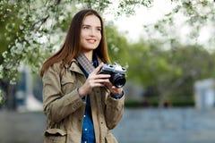 Mujer joven hermosa que usa la cámara de la foto del vintage en el parque Fotografía de archivo