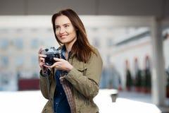 Mujer joven hermosa que usa la cámara de la foto del vintage en la plataforma del ferrocarril Imágenes de archivo libres de regalías