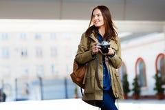 Mujer joven hermosa que usa la cámara de la foto del vintage en la plataforma del ferrocarril Fotografía de archivo