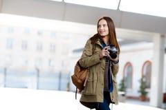 Mujer joven hermosa que usa la cámara de la foto del vintage en la plataforma del ferrocarril Foto de archivo libre de regalías